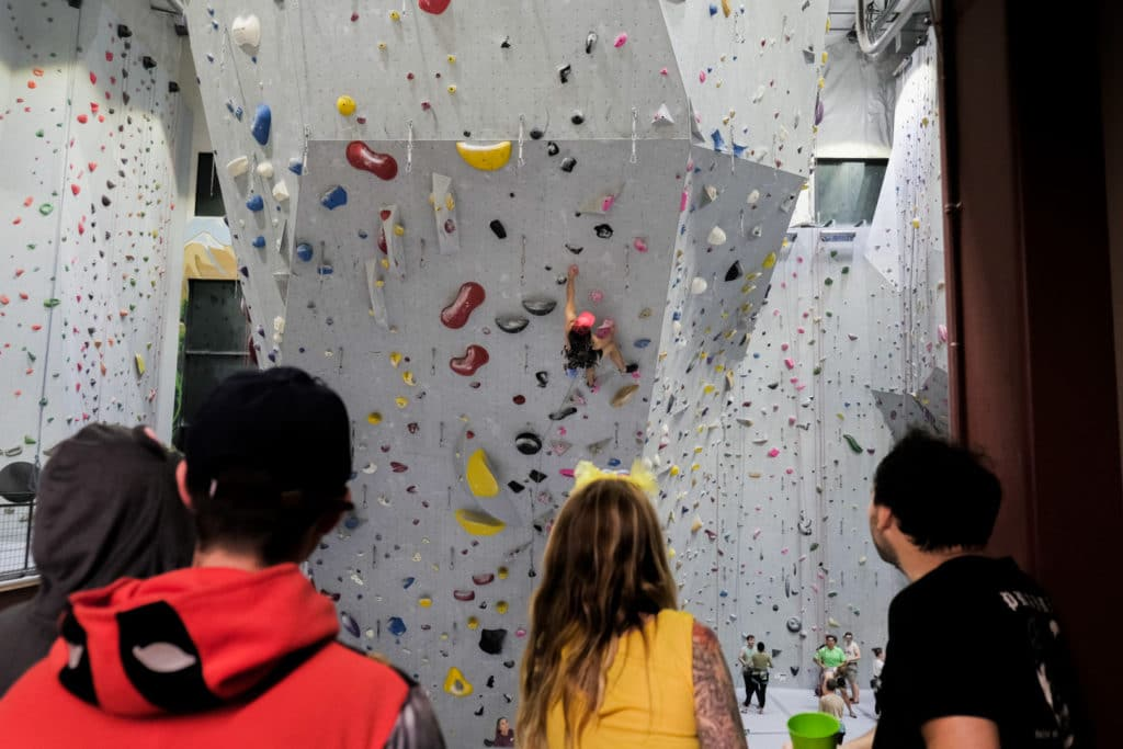 Mesa Rim inspires a safe, non competitive community that helps members to grow and cheer each other on. Here you can see members watching and supporting the climber ahead successfully (Halloween costume and all!) lead climb his way up the wall.